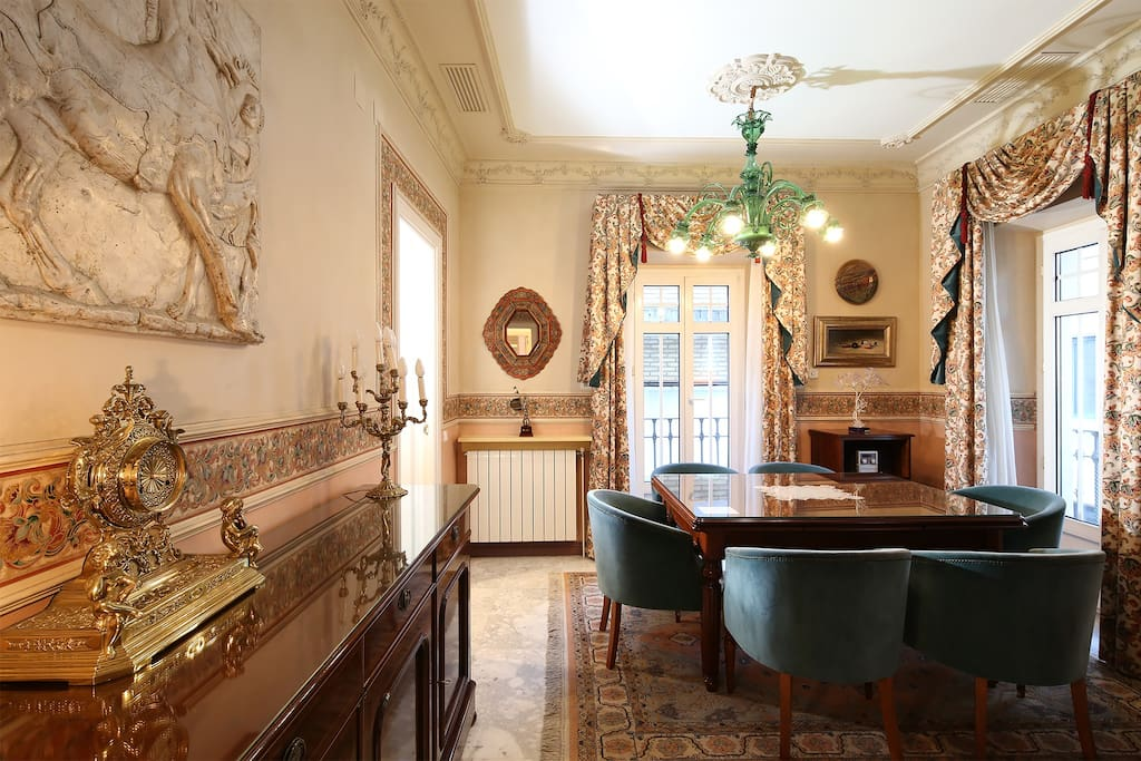 The living-dining area is decorated with dark wood furniture and original artwork.