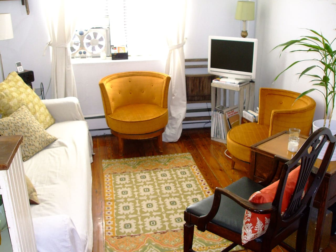 The vibrant, warm and cozy living room.  People feel very welcomed and comfortable here. The orange chairs swivel!