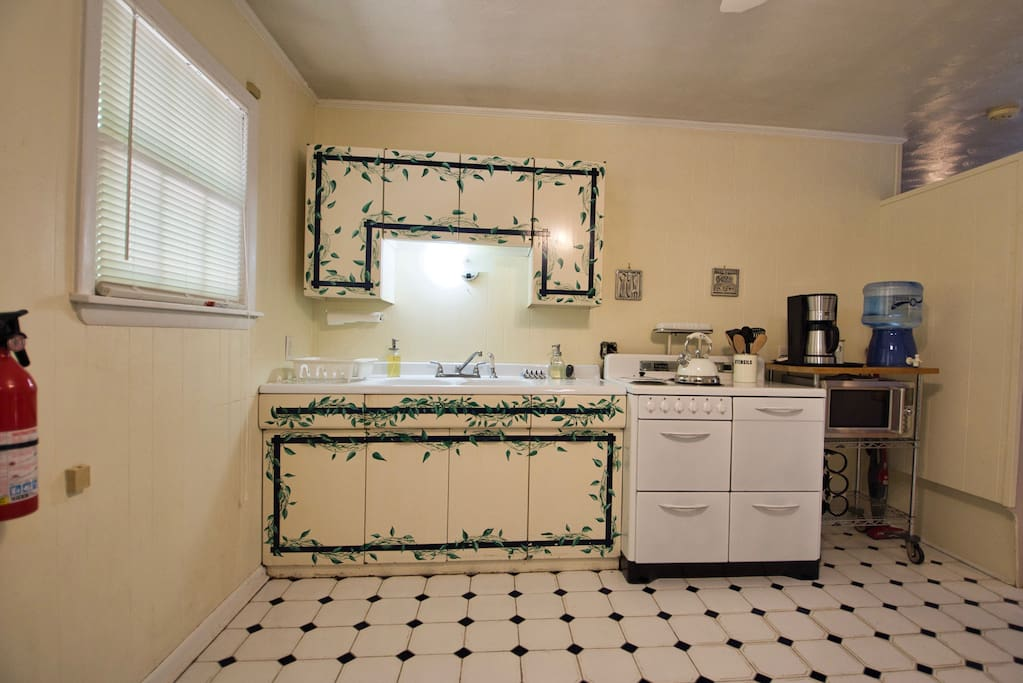 The spacious kitchen features original metal cabinets with enameled cast iron double drain boards and vintage electric Hotpoint stove with soup well.