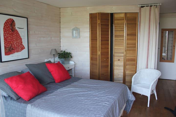 Lit double et salle de bain au fond derrière les panneaux de bois.