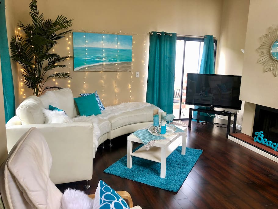 We updated the brown sofa sectional for a fresh white semi circle sofa and an aqua colored beach theme in living room.  Sliding glass doors open to 2 seperate balconies.