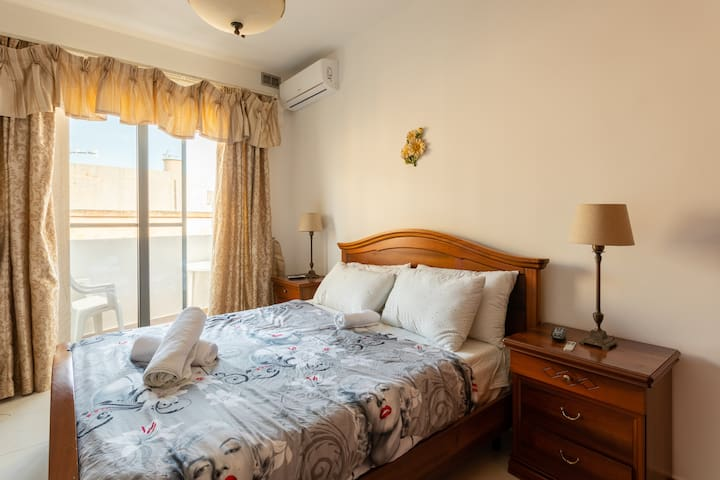 Big and bright bedroom with balcony and double bed.