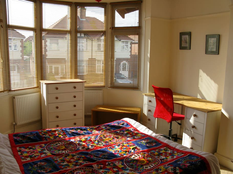 The double room with wooden blinds, desk, chest of drawers & a good sized wardrobe