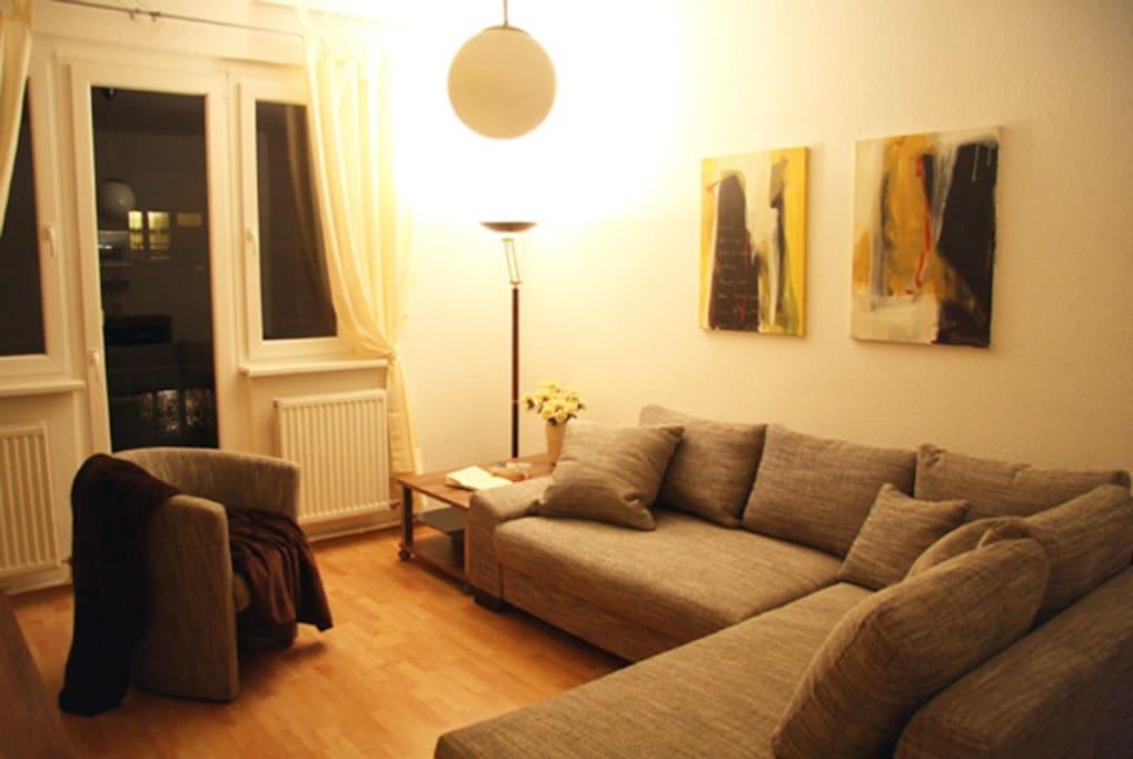 Wohnbereich mit Couch und französischer Balkon.