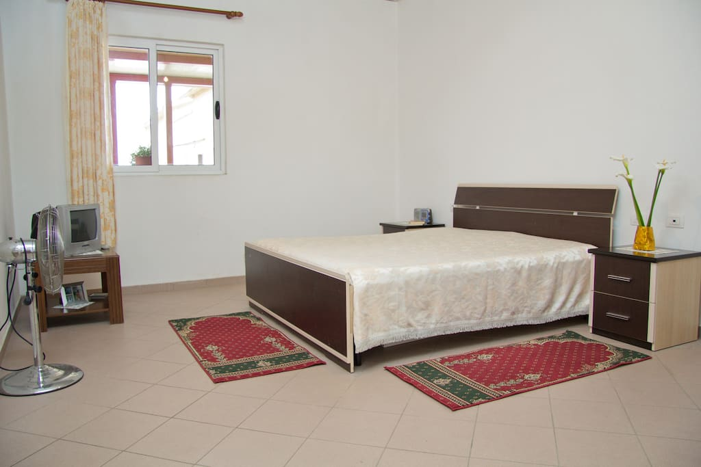 The big bedroom with a queen bed and a single bed