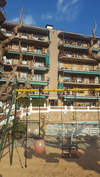 Vista meridional dels apartements amb parc infantil i piscines.