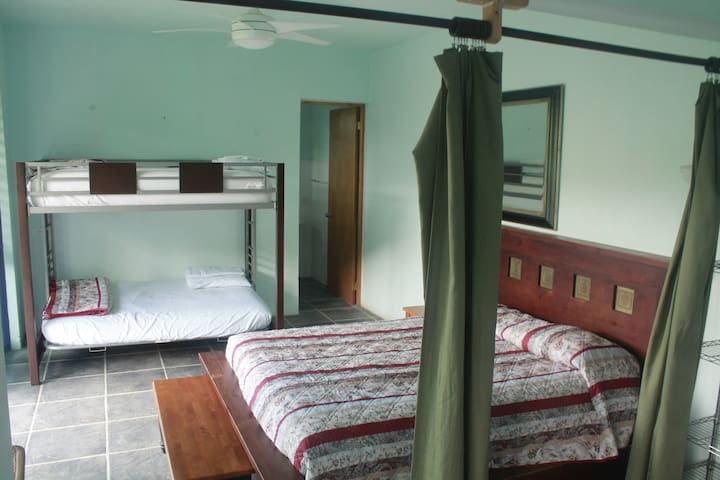 The classic suite with the bunk bed pictured and bathroom entrance. The bathroom has hot water, flushing toilets, a sink, and shower! Fans are located in rooms for increased airflow too.