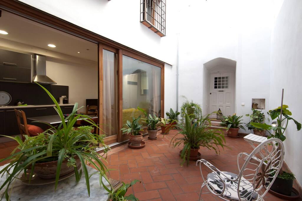 el amplio ventanal que abre el salón al patio, un lugar ideal  para descansar en las horas más calurosas del verano.