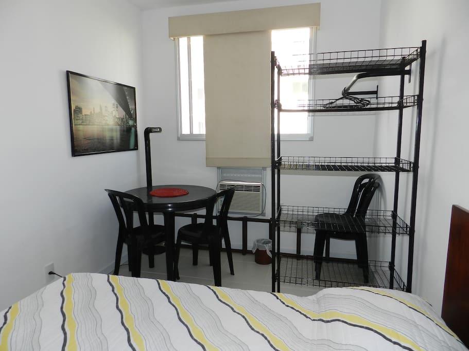 Área no quarto de casal com mesa auxiliar e cadeiras e estante alta.