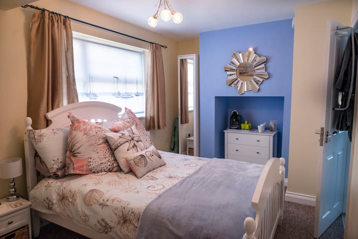 Bedroom view with white wood sturdy bed & beautiful  Happy Friday Bedding, the en-suite shower room is the door that is slightly open