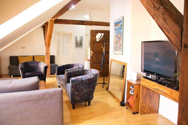 Studio-like living room with TV, sofas, armchairs provides additional space