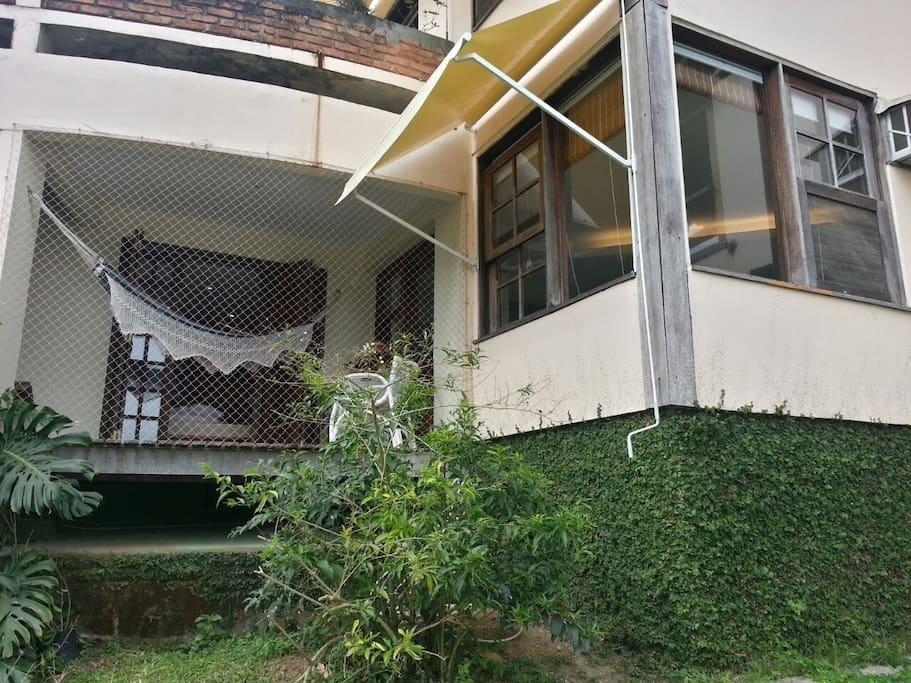 Casa de Hóspedes: sala com o toldo e quarto com varanda telada