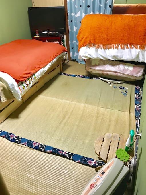 一階真ん中部屋、ベッド二台目折り畳み時。就寝前までは部屋が広く使えます。不用時は玄関部屋に移動させて、お布団を敷き詰めればお好きな人数でご就寝いただけます。冬場は寒いので、エアコン使用前にガスファンヒーターもご利用ください。