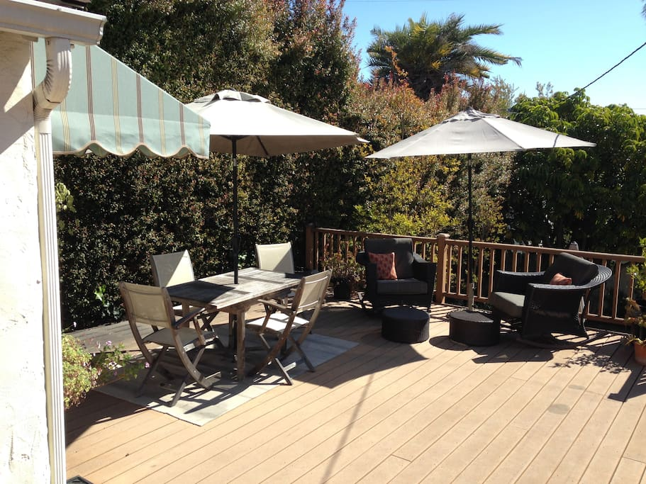 Large deck with table and chairs for lounging.