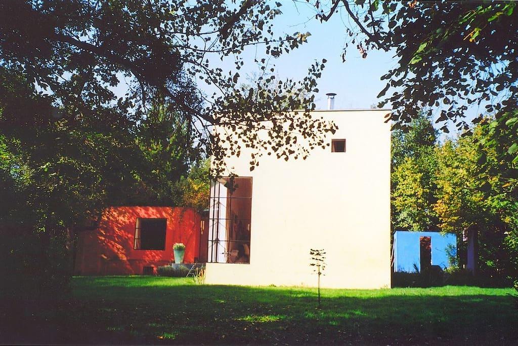 De l'extérieur, le bloc rouge: grande chambre  avec SDB, dressing et WC. Bloc jaune : atelier, cuisine, mezzanine avec chambre d'amis, WC.  la veranda au centre relie les 2 blocs.