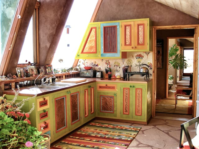 Fun colors, mosaics, and copper accent panels make the kitchen a fun visual treat.