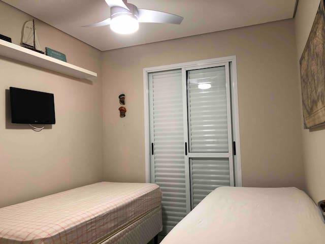 Quarto solteiro com duas camas mais bicama ( acomoda 03 ) Ambiente com ventilador de teto.