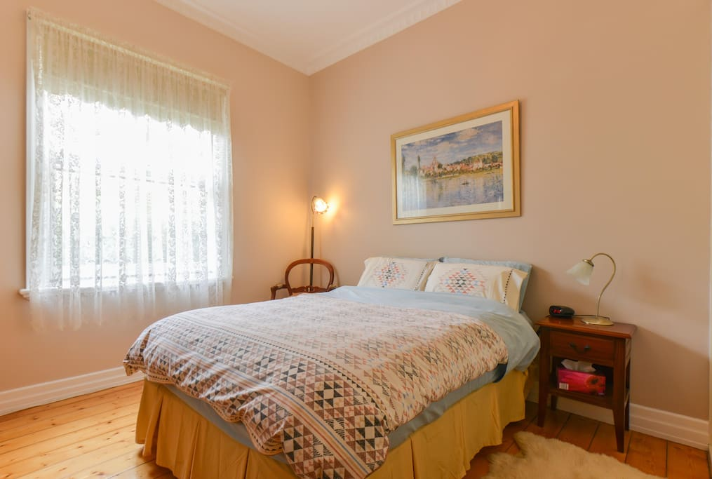 A spacious guest bedroom, freshly decorated.