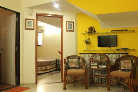 Airbnb SUPERHOST welcomes you to our cosy 1 BHK suite with private entrance - Hall, 1 Bedroom, well equipped Kitchen and a modern clean Bath with Parking, TV & WIFI. Quiet leafy residential place near Colleges, IT Park & Shops helps you feel at home.