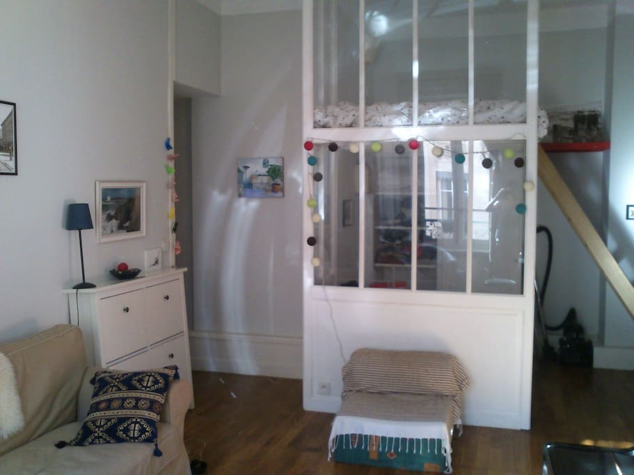 lit en mezzanine séparé du coin salon par une verrière