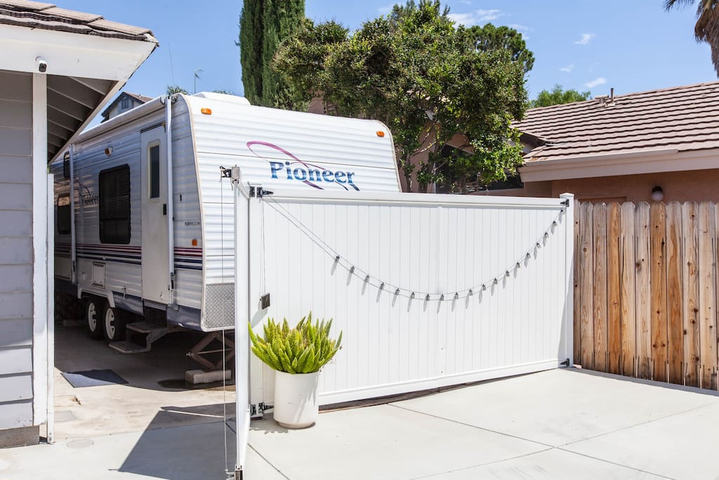 The RV is behind a white privacy fence. This area is away from the main house. Privacy is yours. Come and go as you please