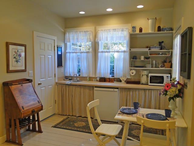 Kitchen area with microwave, fridge, sink & table. Also an outdoor grill. We provide some snacks and/or muffins, coffee (Keurig not pictured but it is there) and wine to get you started.