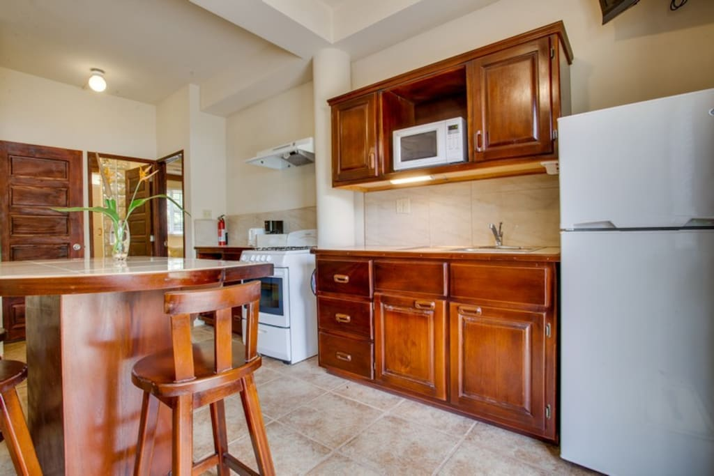 Kitchen with full stove and oven, fridge, microwave and cooking utensils.