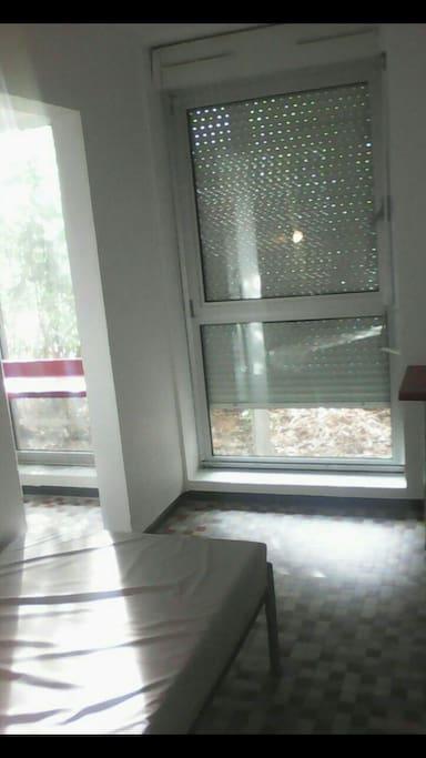 une grande baie vitrée faisant face au lit d'une place.