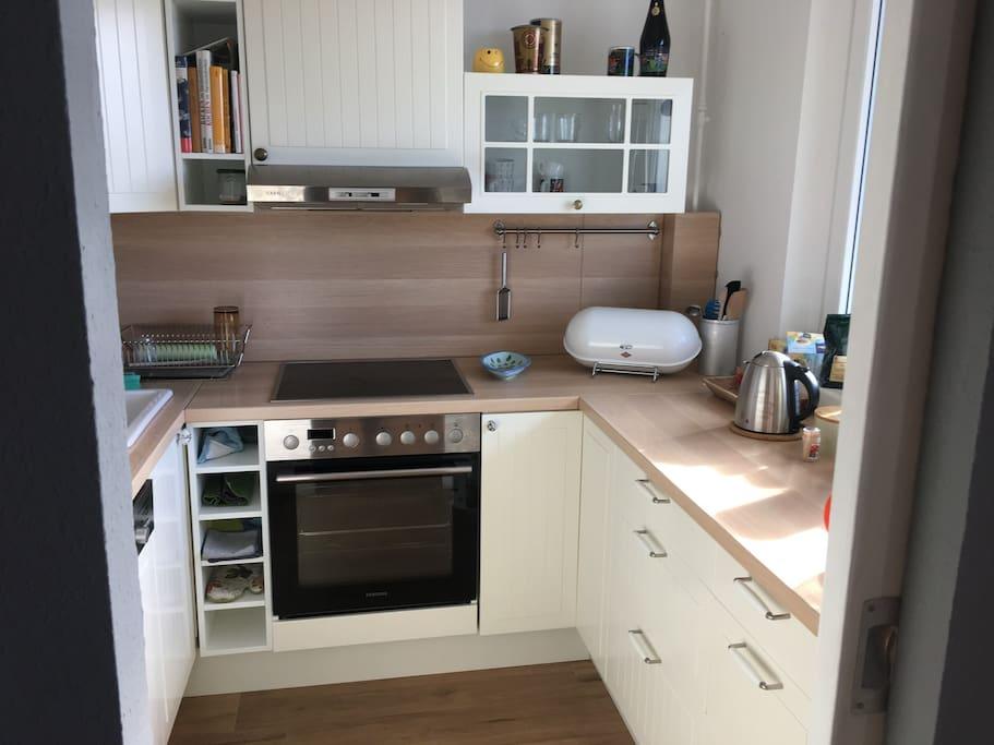 Küche mit Kaffeemaschine, Wasserkocher, Toaster, Herd, Geschirrspülmaschine, Geschirr und Besteck