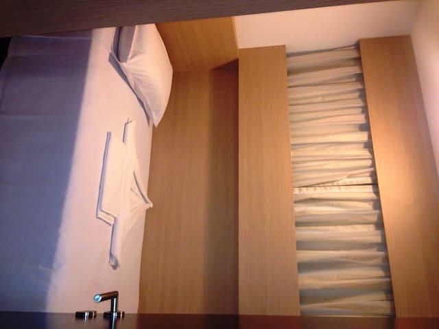 Quarto de solteiro com tv, ar condicionado e armário