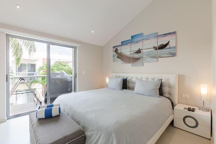 Master king bedroom with lush bedding, TV, safety box, and balcony access.