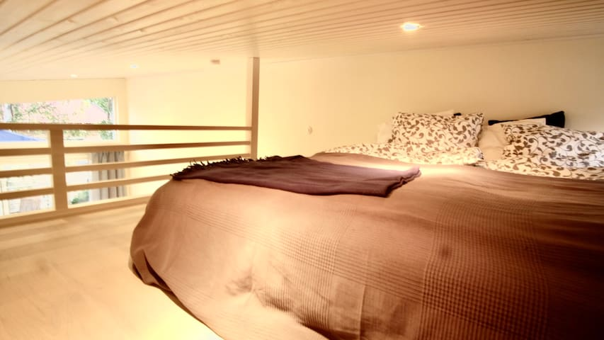 Large sleeping loft with comfortable bed, 180 cm wide. Small window next to bed which can be opened.