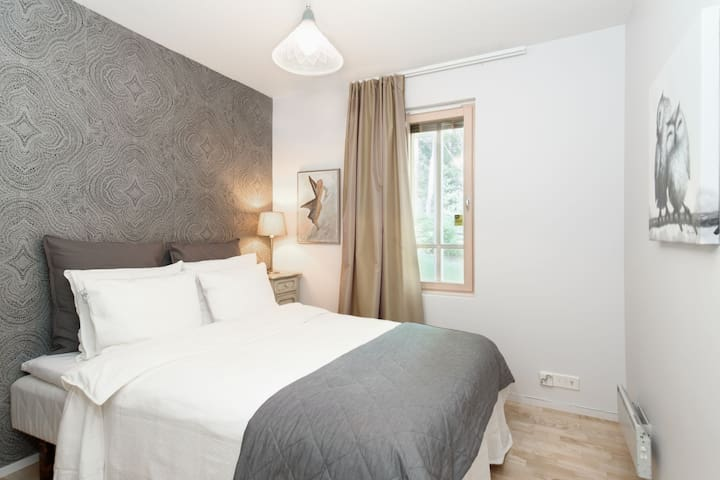 The third sun-filled bedroom with a queen bed and stylish feature wall