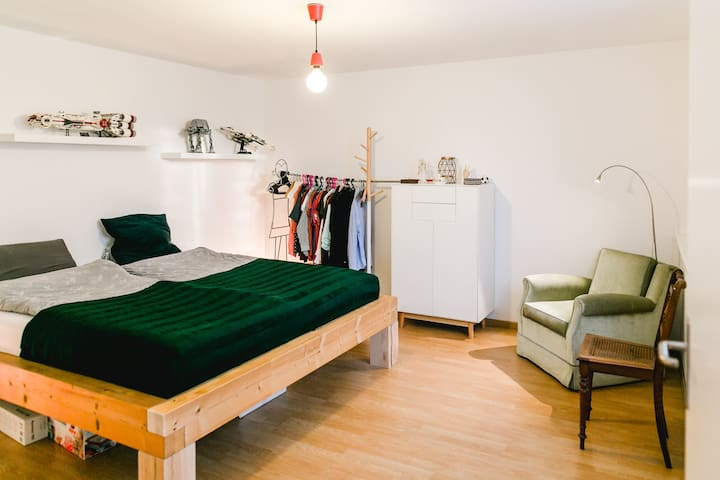 Schlafzimmer mit grossem Bett, Kommode, offenem Schrank und Leseecke. Bedroom with big bed, highboard, open concept storage and armchair to read.