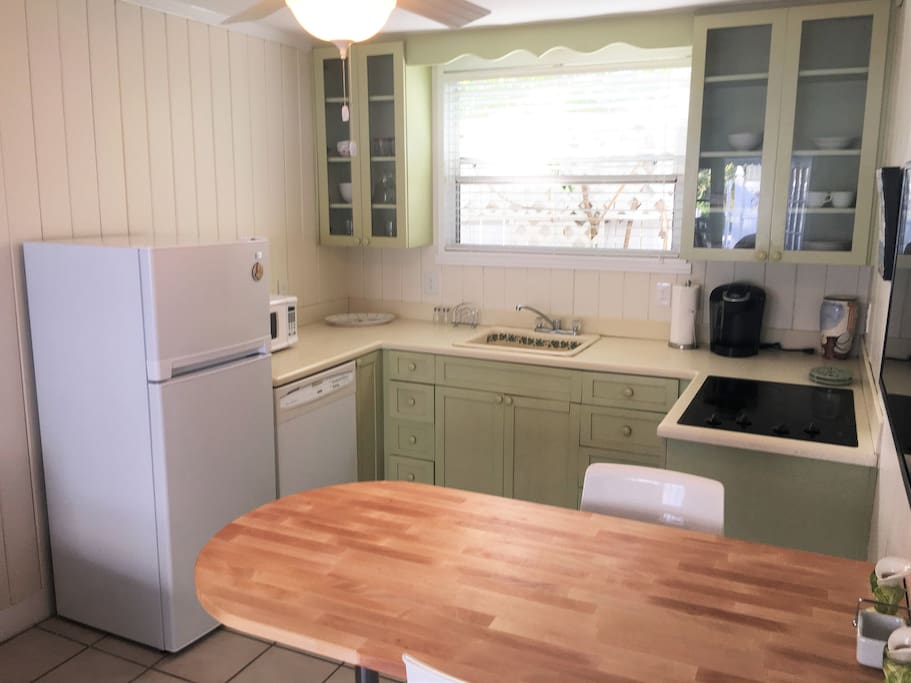 Kitchen with breakfast bar, refrigerator, dishwasher, microwave, and cooktop.