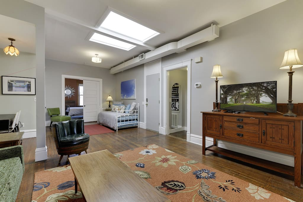 Large 6 ft x 6ft skylight provides loads of natural light. View of daybed with pull-out trundle and larger bedroom in the front of the apartment.