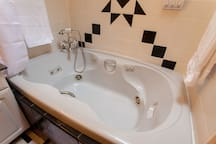 Jetted Jacuzzi two-person tub with luxury fixtures.  Yes we provide luxury shampoo, conditioner and body wash