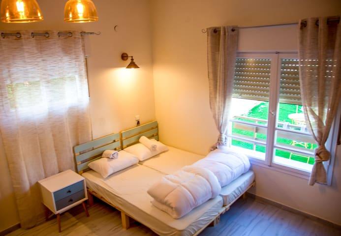 חדר שינה מרווח וחלל מרכזי בקומה התחתונה עם מיטות, סלון, ספה נפתחת ואופציה למיטת תינוק או מיטה נוספת