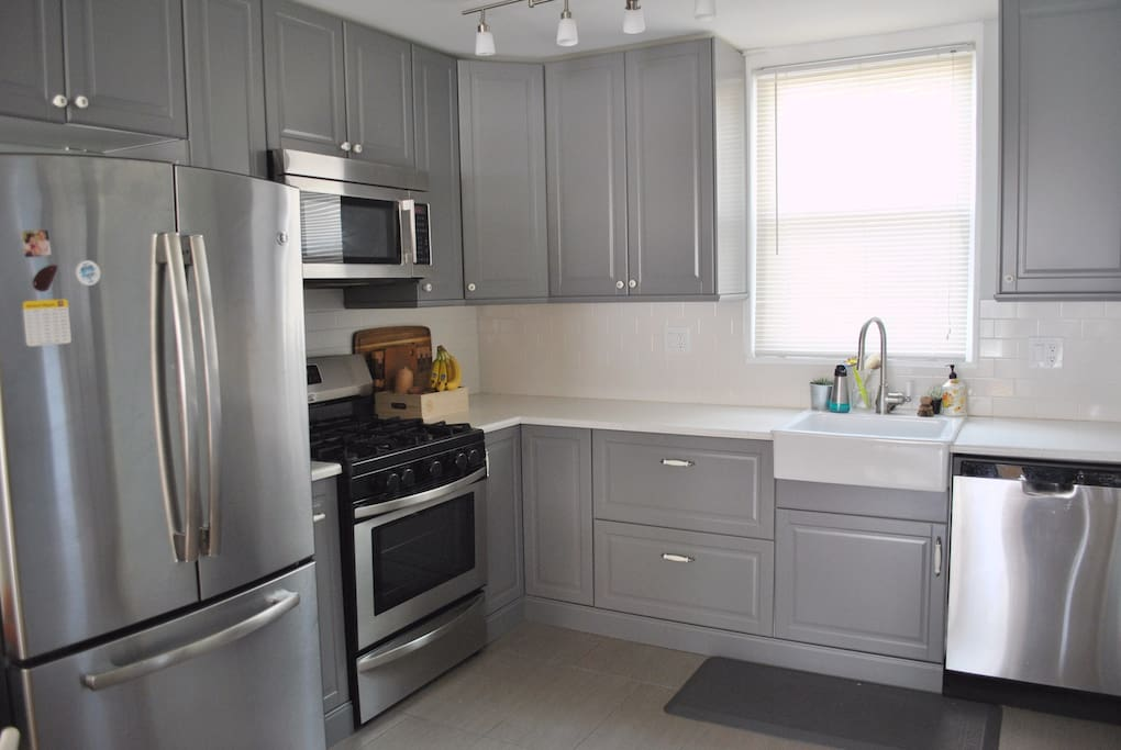 Beautiful and newly renovated kitchen featuring a gas stove, dishwasher, and large refrigerator. Cooking items are stocked - including common spices.