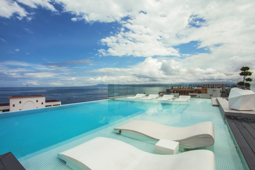 Breathtaking views from rooftop deck featuring infinity pool, two large hot tubs, and bar/lounge areas