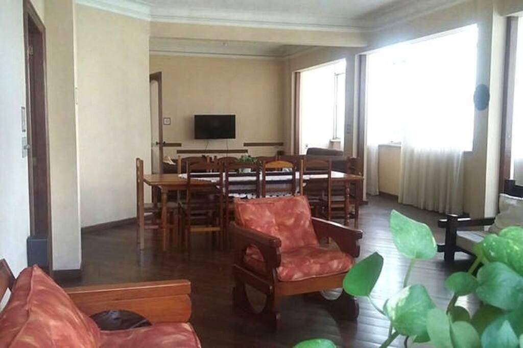 Sala de estar em primeiro plano, de jantar em segundo plano e de TV ao fundo