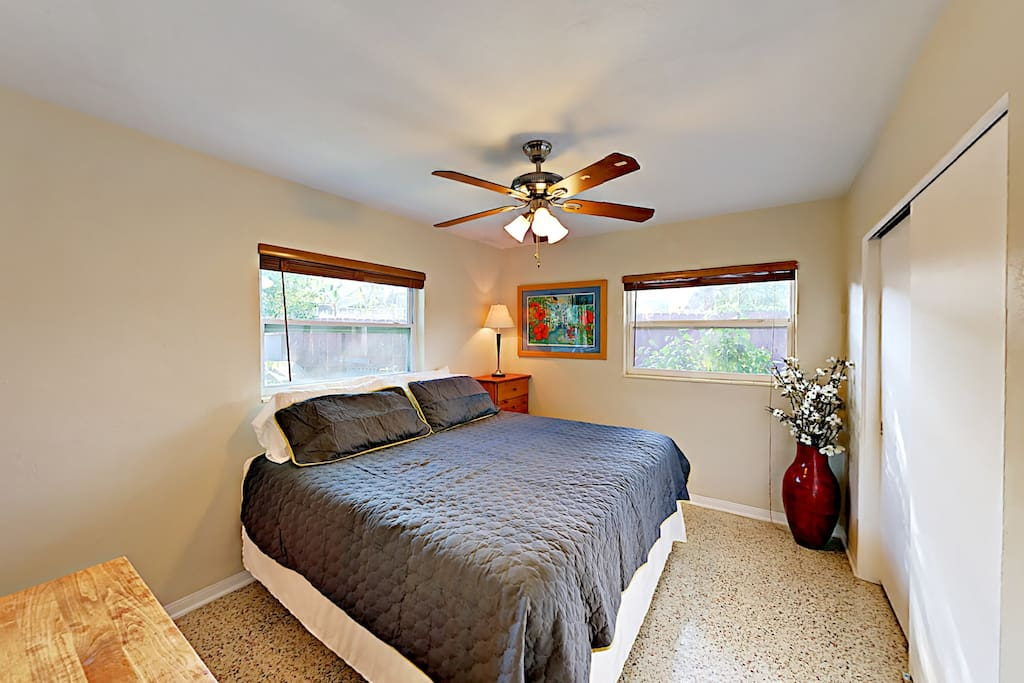 Offering a retro feel, the master bedroom has speckled solid flooring and king bed.