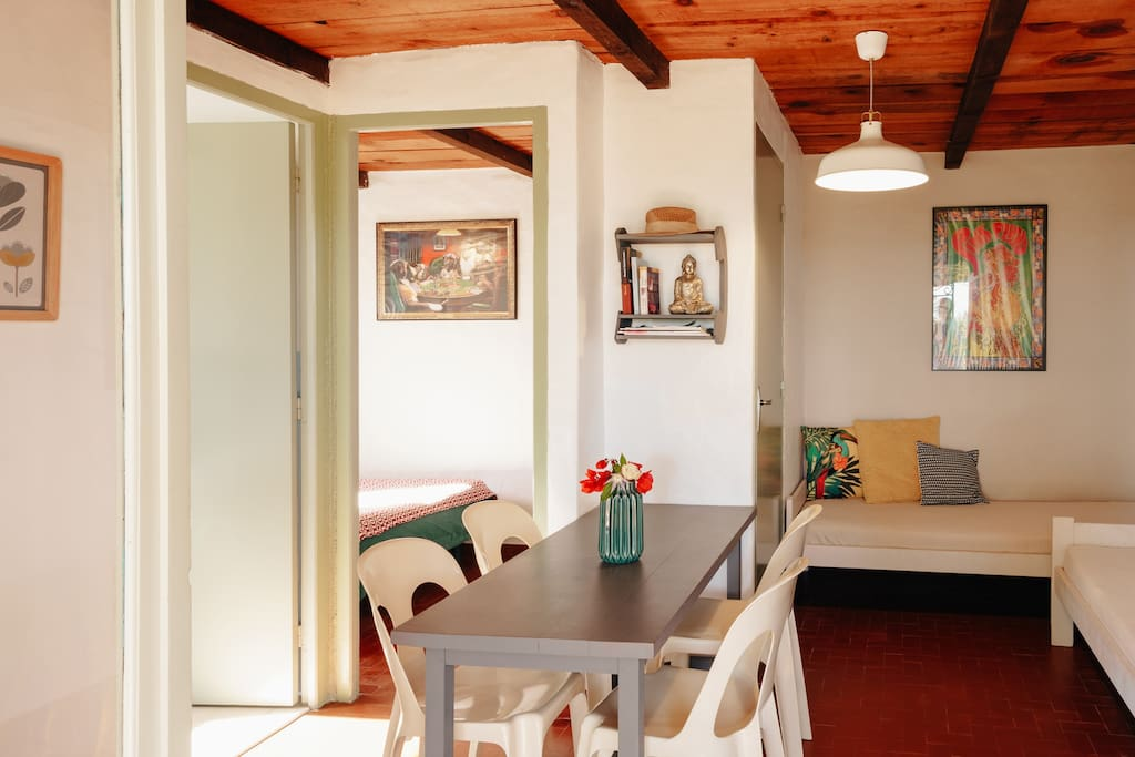 Salon et table de repas avec porte donnant sur la chambre et la salle de douche.