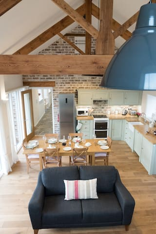 Large, open plan living space with beautiful exposed trusses, hand-made country kitchen and underfloor heating.