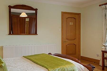 A large bright room with a king bed - Oughterard