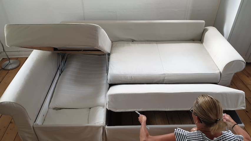 How to prepare the bedsofa: -Remove all loose pillows as well as the back pillows -Move the table and fold the carpet away to make place in front of the sofa -Mount the right bottom section by pulling the two strings towards you, outwards/upwards