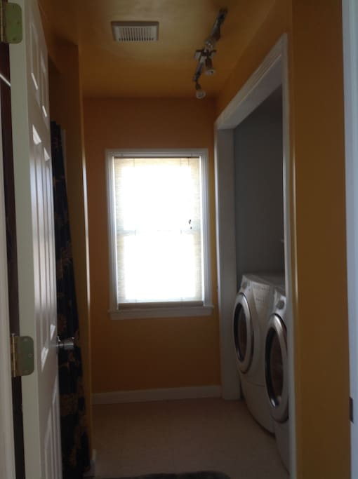 View into bathroom with washer and dryer.
