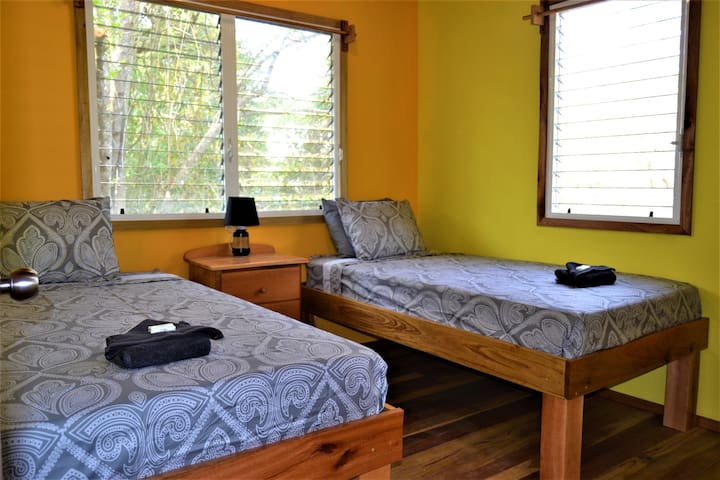 A twin bedroom with a ceiling fan for your comfort