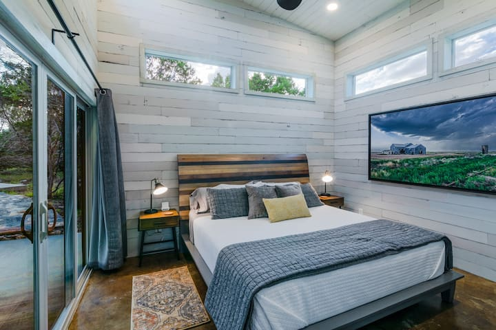 The bedroom features high ceilings with lots of light, and a king-size bed, and blackout curtains. The room features a huge print of a storm rolling into Texas by Hill Country artist Jack Knox.