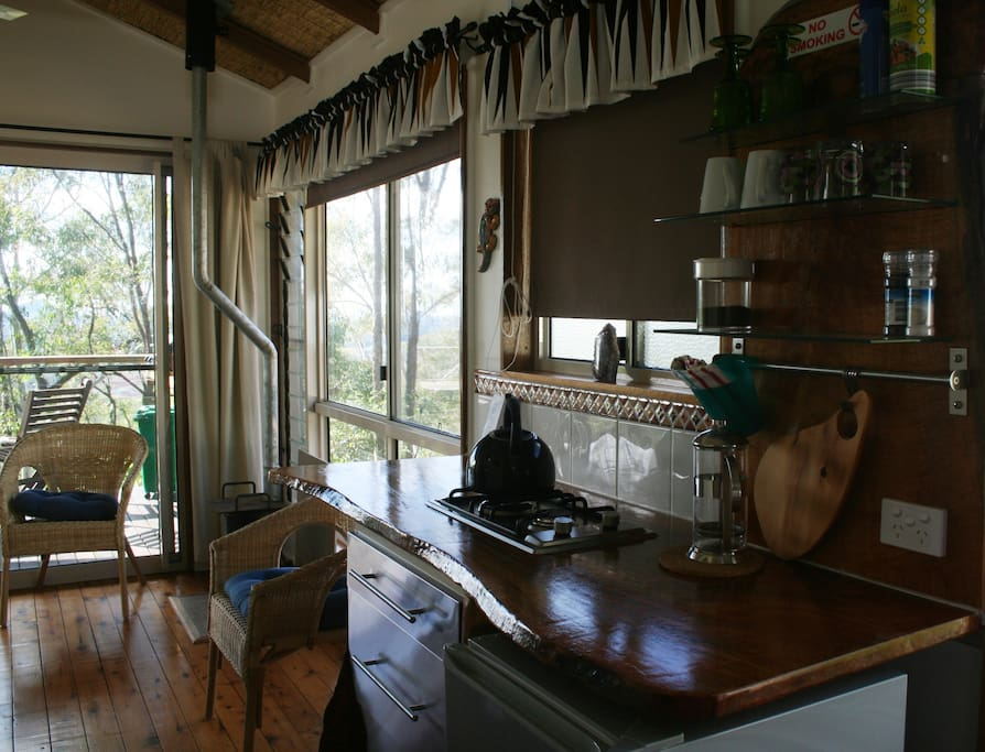 View of the cabin kitchen bench with two burner cooktop/ fridge .